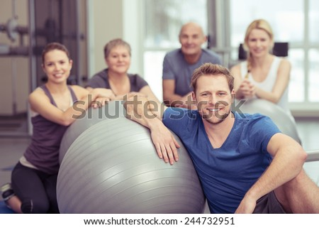 Smiling handsome young man in pilates class at the gym sitting leaning on his gym ball with the rest of the diverse group gathered behind him - stock photo