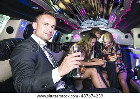 Smiling handsome young man in the back of a stretch limousine, toasting a glass of champagne towards the camera, with three people in the background