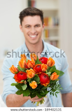 Smiling handsome young man offering a bunch of colorful orange fresh spring flowers to the viewer as a gift on a special occasion - stock photo