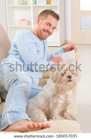 Smiling handsome young man reading storybooks on couch at home with cute maltese dog - stock photo
