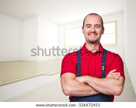 smiling handyman and house interior background - stock photo