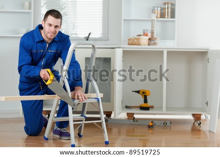 Smiling handyman cutting a wooden board in a kitchen - stock photo