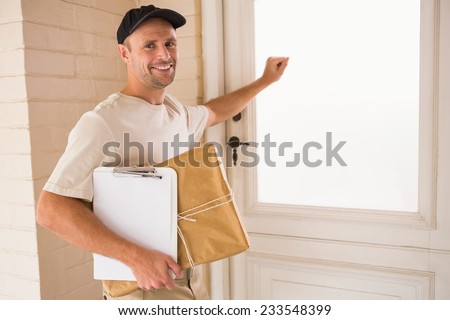 Smiling handyman knocking at the door of someones home - stock photo