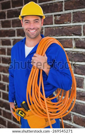 Smiling handyman with rolled wire on white background against red brick wall - stock photo