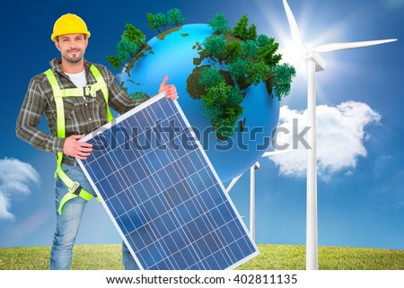 Smiling handyman with solar panel against digitally generated earth floating in air - stock photo