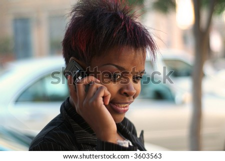 Smiling happy African American businesswoman talking on cell phone in front of new cars - arranging for finance - stock photo