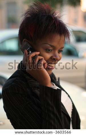 Smiling happy African American businesswoman talking on cell phone in front of new cars - arranging for finance