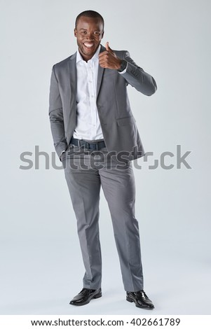 Smiling happy african black businessman giving a thumbs up in studio