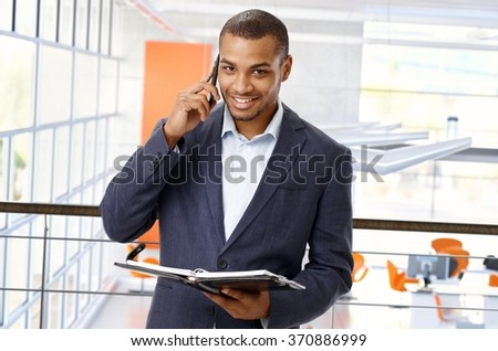 Smiling, happy, afro american office worker at business center with mobile phone and personal organizer. Looking at camera, copyspace. - stock photo