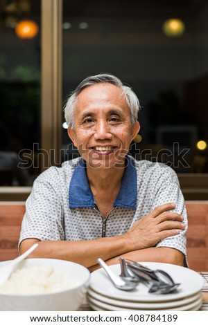 Smiling happy Asian male senior looking at camera.