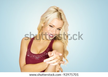 Smiling happy beautiful blonde woman pointing her finger at the camera on blue studio background. - stock photo