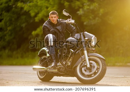 Smiling happy biker in sitting unknown on big chopper bike on road - stock photo