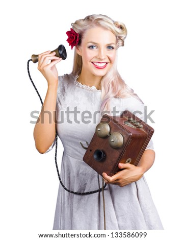 Smiling happy blond woman holding very old antique telephone on white background - stock photo