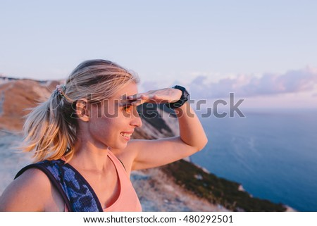 Smiling happy blonde young woman hiker with backpack standing on mountain peak and looking forward with raised hand