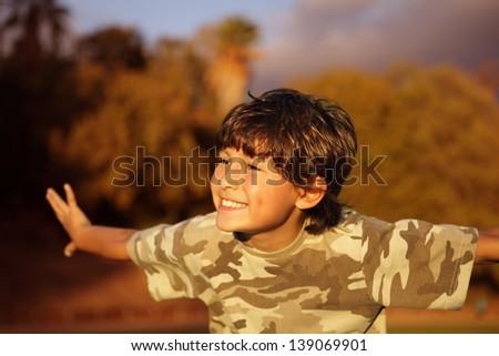 Smiling happy boy at sunset - stock photo