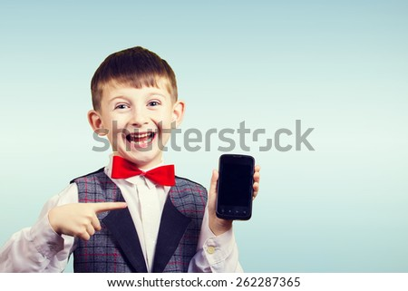 Smiling Happy boy holding mobile phone, looking at camera.Close-up Studio Portrait isolated on blue background. - stock photo