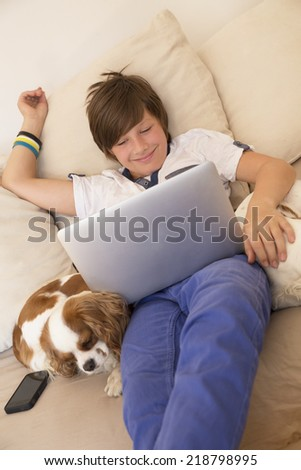 Smiling happy boy watching laptop - stock photo