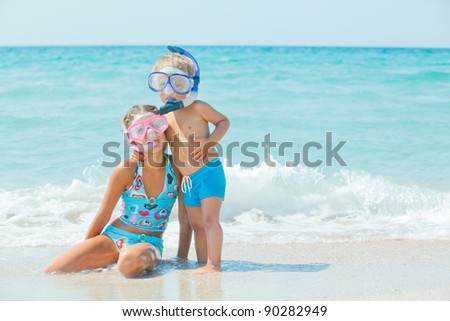 Smiling Happy brother and sister posing on a beach wearing snorkeling equipment. In the background the sea