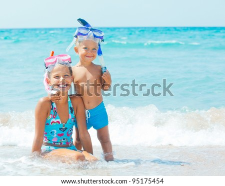 Smiling Happy brother and sister posing on a beach wearing snorkeling equipment. In the background the sea - stock photo