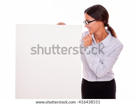 Smiling, happy brunette businesswoman with glasses looking at a placard, wearing her straight hair tied back and a button down shirt, gesturing with her hand on her chin - stock photo