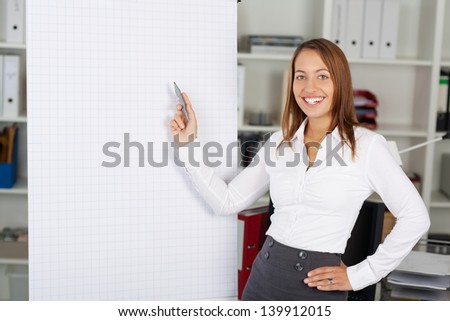Smiling happy business woman in office presentation with a flipchart - stock photo