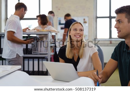 Smiling happy businesswoman talking to a male colleague in the foreground in a busy open plan office with co-workers in the background