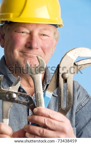 smiling happy contractor builder with tools and construction hard hat protective helmet - stock photo