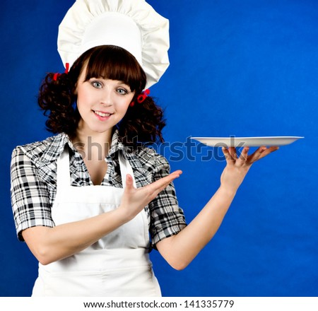Smiling happy cook woman with plate on a blue background - stock photo