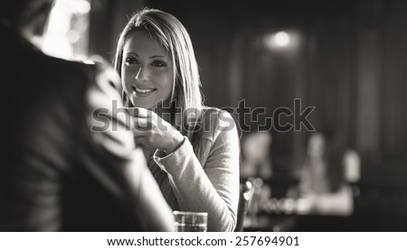 Smiling happy couple at the bar spending time together - stock photo