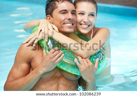 Smiling happy couple in pool with floating ring - stock photo