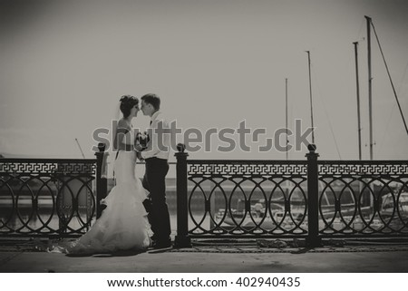 Smiling happy couple on bridge wedding day, the bride in a white dress with a train, a groom in a blue suit. - stock photo