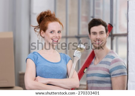 Smiling happy couple renovating their house standing smiling at the camera with paint brushes and tools in their hands, focus to the woman - stock photo