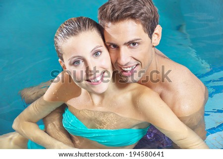 Smiling happy couple sitting in water of a hotel swimming pool - stock photo