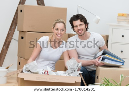 Smiling happy couple unpacking cardboard cartons as they sit on the floor in their new house unwrapping their possessions and smiling at the camera - stock photo