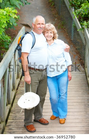 Smiling happy  elderly couple in summer park