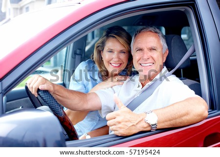 Smiling happy elderly couple in the car - stock photo
