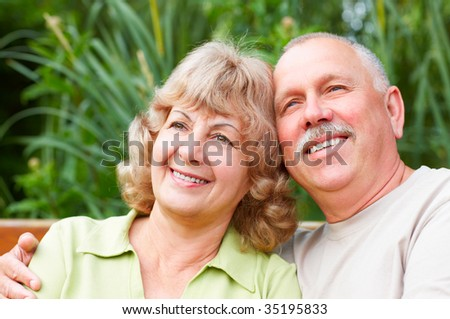 Smiling happy  elderly couple in the summer park