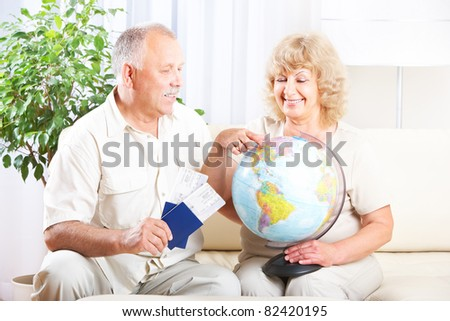 Smiling happy elderly couple with tickets and passports. - stock photo