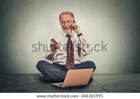 Smiling happy elderly man making order by mobile phone sitting on a floor of his office