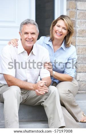 Smiling happy elderly senior couple near the home - stock photo