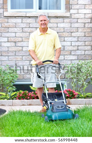 Smiling happy elderly senior man with lawnmower