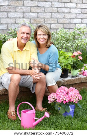 Smiling happy elderly seniors couple gardening near the home - stock photo