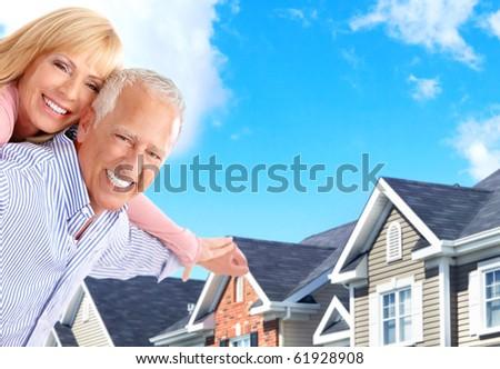 Smiling happy elderly seniors couple near the home - stock photo