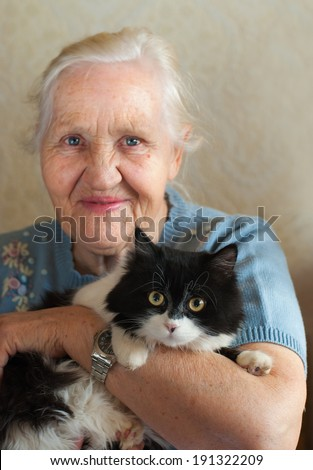 Smiling happy elderly woman with her cat. Selective focus on a cat - stock photo