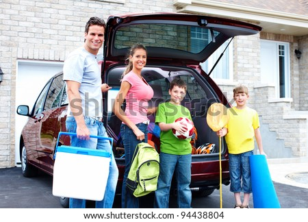 Smiling happy family and a family car. - stock photo