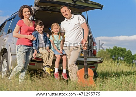 Smiling happy family and their car