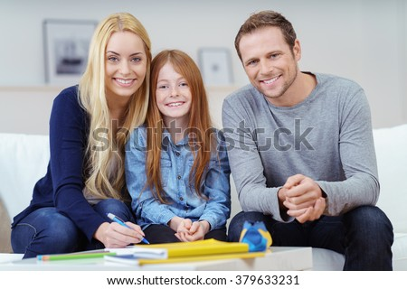 Smiling happy family portrait with two attractive parents sitting on either side of a pretty vivacious young redhead girl on the sofa at home