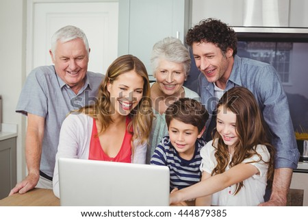 Smiling happy family using laptop in kitchen at home - stock photo