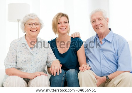 Smiling happy family with granddaughter and grandparents looking together at camera at home - stock photo