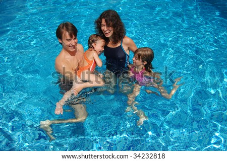 Smiling happy family with kids having fun in swimming pool - stock photo